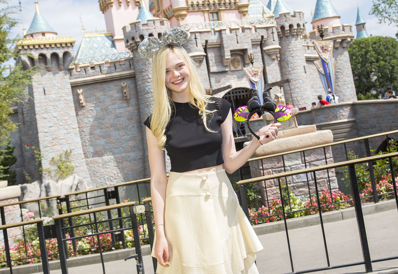 Elle Fanning in front of Sleeping Beauty Castle at Disneyland