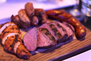 Grilled steak and chicken breast, chicken wings and sausage